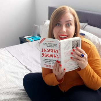 Woman sitting on a bed reading a book, Radical Candor